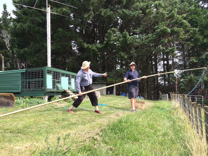 John instructing Stan on how to pole vault over the tree and hang a halyard!!! Actually it was one of the 40M loop support poles